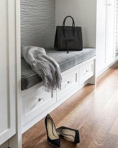 Chic white and gray mudroom features a built-in bench lined with a gray velvet seat cushion flanked by floor to ceiling cabinets.