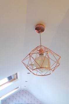 Copper metallic geometric light fitting decor detail in an attic bedroom restyle with a pink and grey colour scheme.