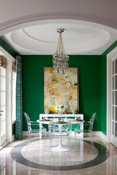 Emerald green walls and curtains bring an intimate, rich feel to this petite dining area. The crisp white tulip table and Ghost chairs keep the attention on the beautiful jewel tones surrounding the space.