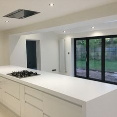 Sleek white open plan kitchen with bi-fold doors and vaulted ceiling, large central island with hob and telescopic cooker hood. Kitchen Island Trim, House, House Inspo, Bifold Doors, New Homes, Open Plan Kitchen, Kitchen, Open Plan Kitchen Diner, Kitchen Extension
