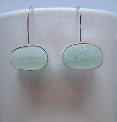 Bottle stopper stems from the coastline of Northern England - trash transformed into treasure! Authentic seafoam green bottle stopper stems have been wrapped in sterling silver and suspended from sterling earwires. The sea glass measures 3/4 across. The earrings are 1 1/8 from the