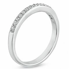 Whether you are celebrating your wedding day, a special anniversary or more simply, your love for her, a simple diamond band makes the perfect gift. Express your feelings for her with this exquisite 10K white gold style. Effortlessly floating across the design, round diamonds totalling 0.12 ct. are truly breathtaking. With every glance, she's certain to think of you.
