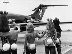Playboy bunnies wave as Hugh Hefners private jet arrives in London. 1970s