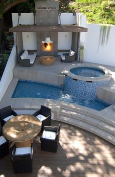 Multi-level patio with fireplace, hot tub, pool, and separate seating areas