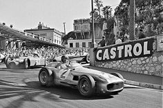 Juan Manuel Fangio leading the pack at the 1955 Monaco Grand Prix in his Mercedes Silver Arrow, with  Louis Chiron's Lancia hot on his heels.  Fangio started from pole and set the fastest race lap, but was forced to retire on lap 50 with transmission problems, and FerraridriverMaurice Trintignantwent on to victory.