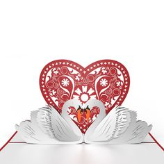 The gorgeous red cover of the Swans Valentine's Day card with its subtle sparkle features a laser-cut depiction of two swans facing each other and forming a heart. Once opened this romantic Valentine'