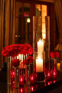 A couple of tall glass hurricanes are paired with romantic red votives and dozens of red roses.