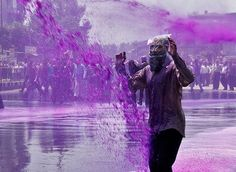 Undeterred by the dye, an Indian government employee wears a plastic bag over his head to shield himself from a police water cannon during a protest in Srinagar. The dye helps police to identify protesters later.
