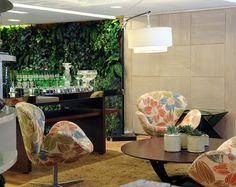As poltronas com estampa floral colorida tornam o ambiente moderno e acolhedor. Destaque para a parede verde ao fundo, que traz ainda mais a natureza ao ambiente. Projeto da designer de interiores Adriana Scartaris.