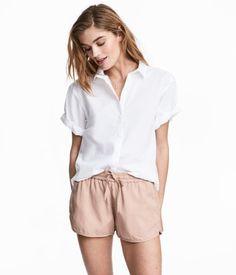 Hvid. Skjorte i let, vævet bomuldskvalitet. Skjorten har krave og skjult lukning foran. Lige pasform. Lav skuldersøm og korte ærmer med fastsyet opslag.