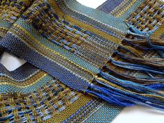 A great scarf to wear to the symphony or with my personal favorite jeans. Measures approximately 4 1/4 x 63 plus fringe. I have handwoven this scarf with rayon, in a beautiful blend of olive, blues, and browns. There are also wonderful little bamboo ribbons woven in. Click here to see my complete collection of scarves: http://www.etsy.com/shop/masonke