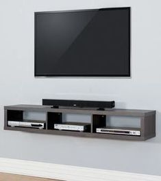 Tv on the wall with remote and PlayStation on a cabinet #WoodworkingPlansTvStand