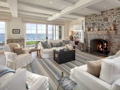 The fireplace in the great room is made from New England Blue Stone and has wood beam accents. Plus, there is an entire wall of French doors for incredible views of the Pacific Ocean.