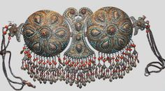 Uzbekistan (probably made in Kiva or Bukhara). Silver-gilt, small turquoises, corals. Truus and Joost Daalder collection, purchased from Linda Pastorino.  Beautifully designed, this is a headdress, which is attached to a very large structure worn on top of the head. The piece is decorated with great finesse and skill. The micro-mosaic pieces of turquoise set off the motifs very well. The tassels are exceptionally good both in design and - *very* exceptionally - in condition.