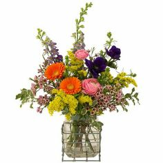 Secret Garden - A casual style design of bright flowers. Here are ranunculus, gerbera, lysianthus, waxflower and solidago, all gathered up into a glass vase with a metal frame. My Flower, Flower Power, Outdoor Flowers, Bright Flowers, Gerbera, Floral Arrangements, Glass Vase, Centerpieces, The Secret