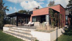 arkitektur 1950-tal tegelhus funkis  Skiffer mot tegelfasad, stenlagd altan, växtbäddar, svarta snickerier mot rödbrunt tegel.