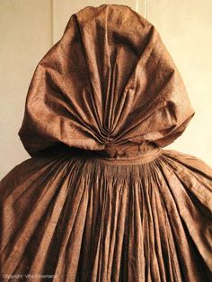 """Amazing jacket pleated """"Polish"""" glossy chintz of the late eighteenth century. The Indian top is ice percale tone on tone with a fine mesh vegetated blister cartridges oblique lines simulating weaving twill and lace background. The inner liners are reuses of older textiles including cotton and chintz thousand lines to tan background. Large hood gently folds cannon mounted on the envelope. Finely pleated ruched generous 18 cm around the cape and hood. Perfect condition and color retention."""