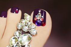 Holiday elegant purple pedicure with rhinestones on a black background with jewelry