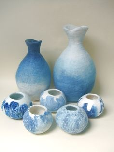 The two larger felt vessels are ombre dyed with indigo, while the five smaller ones are nuno felted with a different yarn or fabric, also dyed with indigo. -by Kim Winter