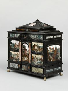 Cabinet, Prague ca. 1610. Castrucci Workshop. Ebonised and gilded wood, and pietre dure. Height: 48.5 cm, Width: 46.8 cm. A rectilinear collector's cabinet with a pyramidal roof, on four lion's paw feet, the front and sides set with seven pictorial pietre dure panels depicting landscapes, buildings and a Venetian canal scene. The Rosalinde and Arthur Gilbert Collection -Victoria and Albert Museum-