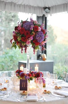 Pink and red roses, purple peonies, burgundy Calla lilies and bunches   of grapes top clear pedestals in these elegant centerpieces.