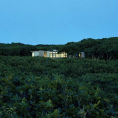 """Residential Architecture: MV House by Architecture Research Office: """"..Martha's Vineyard House frames the transition from land to the strong horizontal datum and vast open space of the ocean. The house is situated against a gentle hill at the southern edge of a clearing in the woods, which offers an expansive view of the water. Three blocks containing different domestic programs are arranged to define a series of exterior spaces, including a protected entry court partially enclosed by the…"""
