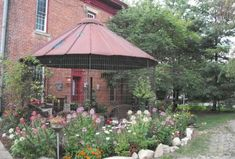 """Myra Glandon's gazebo is made out of an old metal corn crib. """"We call it the cornzebo. We positioned it outside the kitchen door of our old brick house."""" ."""