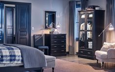 A bedroom with a black chest of 4 drawers, mirror and a wardrobe with tempered glass doors.