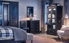 Ein Schlafzimmer mit Bettgestell, Spiegel und Kleiderschrank und UNDREDAL Kleiderschrank in Schwarz mit Glastüren