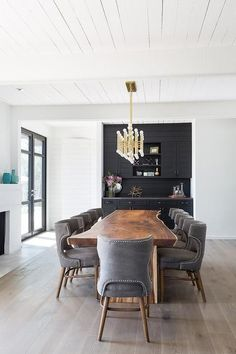 A Jonathan Adler Meurice Rectangular Chandelier hangs from a white plank ceiling over a live edge dining table placed on gray wash floors surrounded by dark gray dining chairs accented with a nailhead trim and complementing a built-in black bar in this chic contemporary dining room.