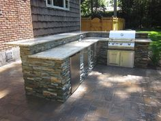 Outdoor Kitchen with Raised Bar veneered with East West Stone - Bayside Waters - Equipped with Brahma Grill Access Doors Sink w/ Access Door Trash Drawer and Refrigerator-Electrical outlets in backsplash - Dix Hills Long Island NY Outdoor Kitchen Countertops, Outdoor Kitchen Bars, Outdoor Kitchen Design, Granite Countertops, Outdoor Kitchens, Backyard Kitchen, Granite Kitchen, Kitchen Island, Gray Granite