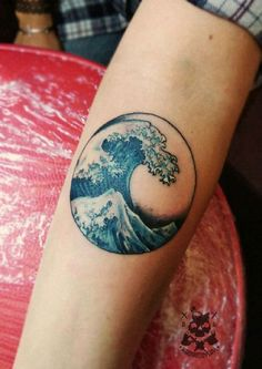 Majestic wave tattoo in a circle frame. The wave inside the circle is drawn tall and strong as it is able to overcome the waters an stand on its own.