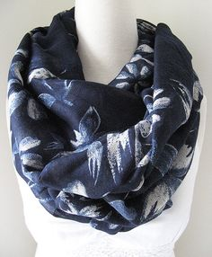 This navy blue infinity scarf is super soft and lightweight. It features lily flowers in white print, and the look is very classy and feminine.  It feels extremely comfortable on your neck, and is a perfect light scarf for spring, summer and fall.     To wash this delicate and soft scarf, simply place it in cold light soapy water, and avoid any harsh detergent or chemical. Then rinse it carefully by hand, and hang to dry naturally in the shade. Please do not twist or place it in the dryer…