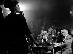 Billie Holiday with Duke Ellington looking on from audience.