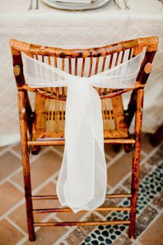 a strip of white linen dresses up the back of a chair. Great for bride and groom, bridal party or all of the chairs, depending on how much linen you would like to use