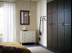 Ein Schlafzimmer mit PAX Kleiderschrank in Schwarzbraun mit HEMNES Türen in Schwarzbraun, KOPPANG Kommode mit 3 Schubladen in Weiß und hochflorigem VITTEN Teppich in Weiß