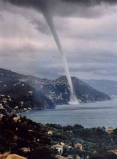 So how do we classify a powerful waterspout when it hits land and is technically then a tornado? This extremely long funnel cloud is an unusual photo, being along a beach rather than either completely  in the water or on land.  http://www.pinterest.com/DianaDeeOsborne/power-beyond-us