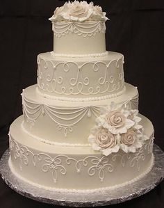 ivory buttercream frosting with white scroll on all layers. Large ivory buttercream roses with white leaves.