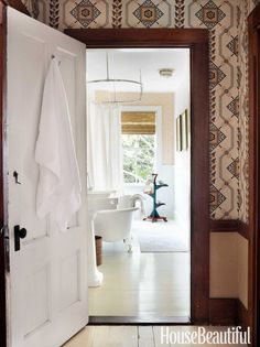 White-painted wainscoting, a pedestal sink, and a claw-foot tub give the master bath a timeless appeal.   - HouseBeautiful.com