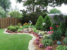 Backyard flower gardens. Love the rock border.
