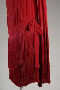 Evening Gown, c. 1925  Silk chiffon with silk fringe     This garment is one of the best examples of flapper-style dress in the museum's collection. The flat silhouettes, use of fringe, and sparkling embroidery are common features of the era.
