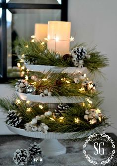 """Cake Stands from Decor Steals- 8"""" - 10"""" - 12"""" in diameter I started with long, casual pine needles then added snow coated pine cones, white berries, silver and pearl Christmas balls and darling white star lights. In the top tier I added a big candle Lots of sparkle and glow! Tip - Make sure to use adhesive putty between the layers to keep the cake plates from moving around or toppling over. I get my adhesive putty at my local craft store. #christmastiered #christmas #tiered #winter"""