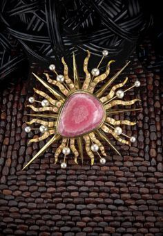 Sunburst Monstrance brooch made of rhodochrosite cultured pearl enamel and 18K gold by Tony Duquette