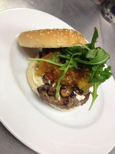 Hamburguesa de filete con piña caramelizada, queso de cabra, champiñones y arúgula.