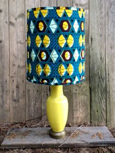 Rich yellow antique porcelain lamp with brass base. Large, hand-made drum shade sporting an African cotton wax print with teal, yellow, dark brown and white. Handsome pairing for a strong splash of color. Tribal, yet refined.