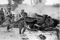 Finnish soldiers marching next to a destroyed Soviet T-34 tank, Battle of Tali-Ihantala, Finland during WWII. c.1944