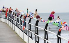 """Unidentified """"yarnbomber(s)"""" leave an Olympics-themed knitted wonder on the railing in a seaside town in England.  Amazing detail!"""