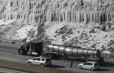 Thick ice has created a waterfall effect on a hill as traffic moves south on I-75 in Covington, Kentucky where temperatures remain in single...