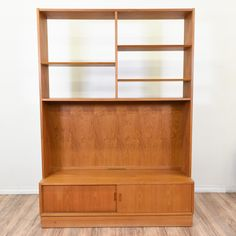 "This ""Hundevad"" bookcase is featured in a solid wood with light teak finish. This danish modern bookshelf is in good condition with top display shelves, a bottom cabinet and space for a large tv. Stylish storage piece perfect for books and electronics! #danishmodern #storage #bookcase&shelving #sandiegovintage #vintagefurniture"