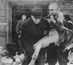 A boy whose whole family perished at the hands of the Germans and who was himself consigned to death at the Auschwitz (Oswiecim) extermination camp, but the Nazis - then beating a fast retreat -  did not have time to burn him. The anguished orphan, now in Lodz, is shown as he was taken out of the one of the smaller crematoriums into which he had been placed by the Hitler pyromaniacs. The two men and the one standing behind are Jews, former inmates of the extermination camp.